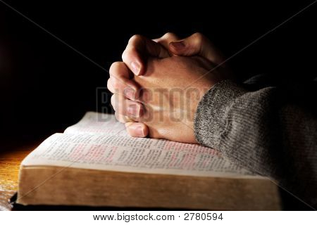 Hands of a man praying in solitude with his Bible (Christian image shallow focus). poster