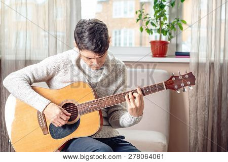 Young Attractive Musician Sitting On A Chair Playing Acoustic Guitar. Concept Of Music As A Hobby