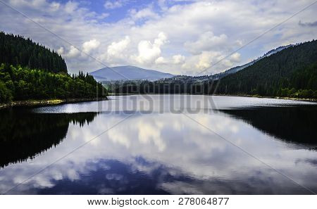 Beautiful Oasa Lake Between The Mountains Mirroring The Clouds And The Sky, Transalpina Road, Romani