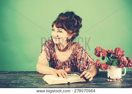 Old Woman Reading Book With Glasses At Flowers. Pension And Retirement, Old Age. Happy Old Lady Or G