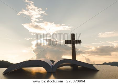 Open Bible, Script In Blur With Focus On Palm Cross,on Sunrise Background, Crucifix, Symbol Of Faith