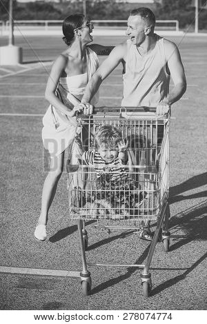 Couple Pushing Shopping Cart With Children In. Family Shopping Concept. Happy Parents Go Shopping Wi