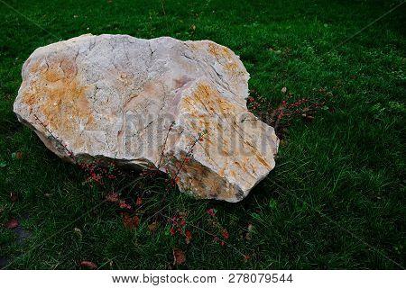 Big Gray Brown Stone Lies On Green Grass