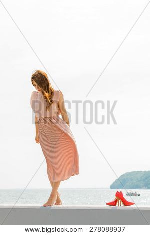 Hobby, Idyllic Aspects Of Femininity Concept. Woman Walking On Jetty Without Shoes Wearing Beautiful