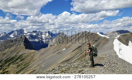 A female hiker backcountry hiking through the remote, secluded, and beautiful rocky mountains in Kananaskis, Alberta, Canada.  This hike is along the Northover Ridge with an incredible ridge walk, amazing valleys, rivers, snow melts, and forests.