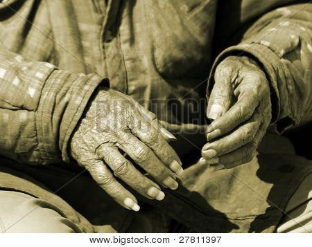 Hands of an old man who sits alone passing time, time that appears to be running out