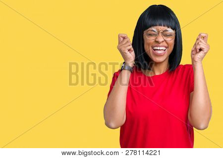 Beautiful young african american woman wearing glasses over isolated background excited for success with arms raised celebrating victory smiling. Winner concept.