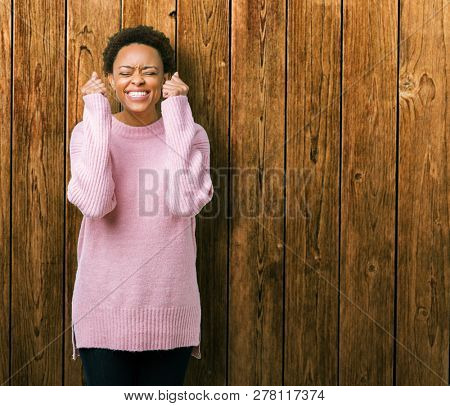 Beautiful young african american woman over isolated background excited for success with arms raised celebrating victory smiling. Winner concept.