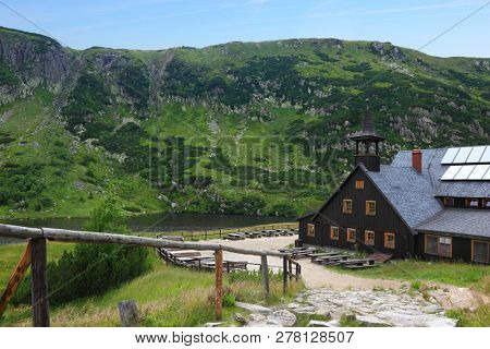 Wooden shelter Samotnia and lake Maly Staw in polish mountains Karkonosze