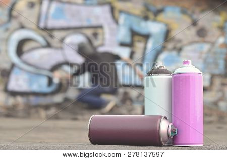 A Still-life Of Several Used Paint Cans Of Different Colors Agai