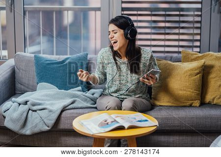 Cheerful woman listening to music with large headphones and singing.Music therapy,mood beneficial pr