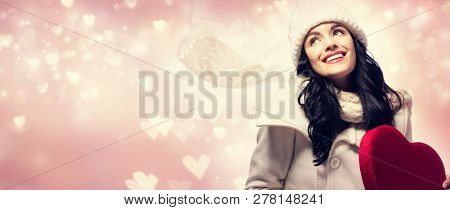 Happy Young Woman Holding A Big Heart Gift Box