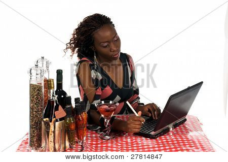 Pretty young African American business woman working on a laptop computer while enjoying a beverage at an Internet Cafe