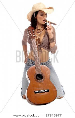 Super sexy rodeo cowgirl in torn jeans, boots and cowboy hat with an acoustic guitar and smoking a big cigar
