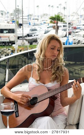 A casual  young woman playing guitar on a yacht in the harbor