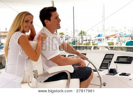A young couple on the fly bridge of a private yacht and looking out to sea as they pull out of the harbor
