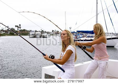 Two sexy young blonds fishing on a yacht hooked up to  large fish