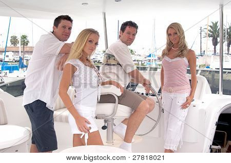Two young couples on a private yacht leaving the harbor