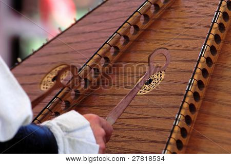 Detail of a man playing a Hammered Dulcimer