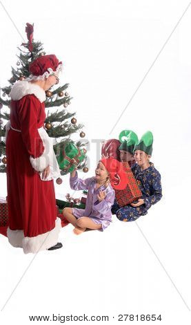 A group of excited children sitting under the Christmas Tree as Mrs. Santa Claus arrives and begins to hand out the gifts.