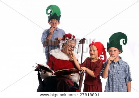 A group of children gathered around Mrs. Santa Claus sitting in her rocking chair and reading them a story take a break to share some chocolate chip cookies.
