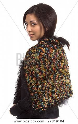 Beautiful young Mexican woman in jeans and a black shirt and a Black couture feather wool shawl woven through with a rainbow of satin ribbons looking back over her left shoulder