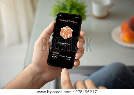Man Hands Holding Phone With App Tracking Delivery Package On The Screen In Room Of The House