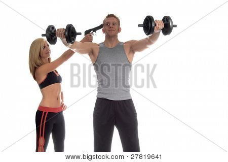 Personal trainer with an unusual style of motivation holding a gun to her male client's head to get him to workout