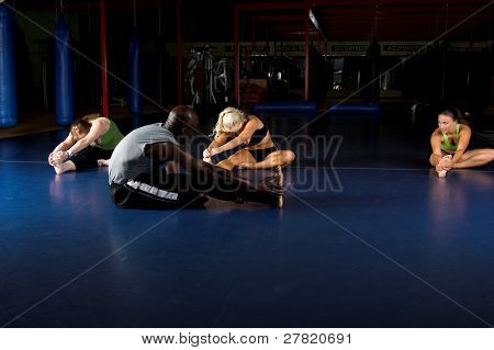 Womans MMA team and trainer stretching out during a warm up in a boxing gym