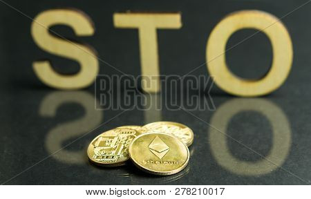 Security Token Offering Sto Sign With Wooden Letters And Gold Coins In Front Of It, Ethereum Concept