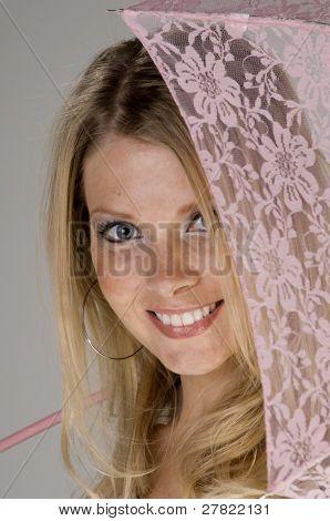 Close up portrait of a beautiful young woman with a pink lace parasol over her shoulder