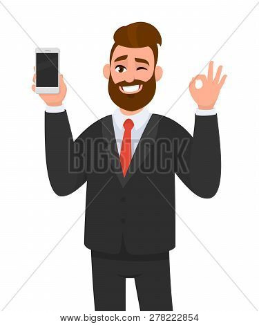 Happy Successful Businessman Showing Smart Phone, Mobile, Cell Phone In Hand And Gesturing Okay Or O