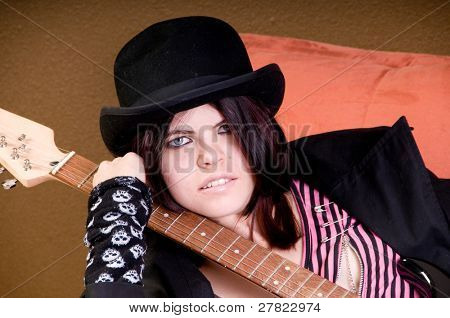 Beautiful and hip scene girl with red and black hair in a pink striped off the shoulder top, pirate sleeves and a felt bowlerwith an electric guitar relaxing on a couch