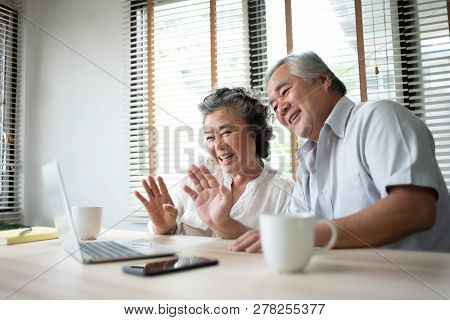 Happy Asian Senior Couple Making Video Call With Their Family By A Laptop Computer Technology.
