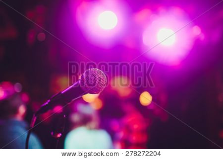 Microphone On A Stand Ready For Live Music Performance Or Karaoke Night With Soft Bokeh Lights And P