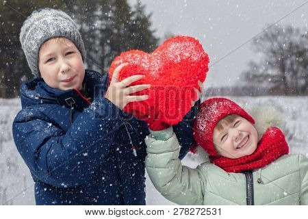 A Smiling Teenager Boy And A Happily Laughing Little Kid Are Holding Both A Huge Red Heart At The Sn