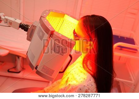 Red Light Therapy. The Girl Goes Through A Course Of Skin Rejuvenation With The Help Of Red Light Tr