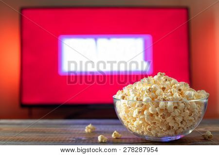 A Glass Bowl Of Popcorn And Remote Control In The Background The Tv Works. Evening Cozy Watching A M