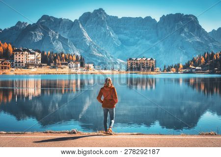 Young Woman Standing On The Coast Of Misurina Lake At Sunrise In Autumn. Dolomites, Italy. Landscape