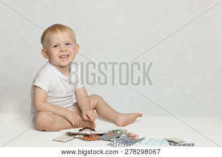 A Toddler Boy Sits On A Rug, Laughs And Plays With Pills And Medicines On A White Background.