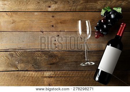 Red Wine Bottle With Grapes And Wine Glass On Brown Rustic Wooden Table Flat Lay From Above With Cop