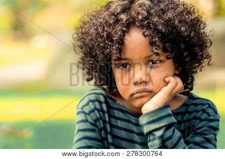 Unhappy Little African American Kid In The Park.