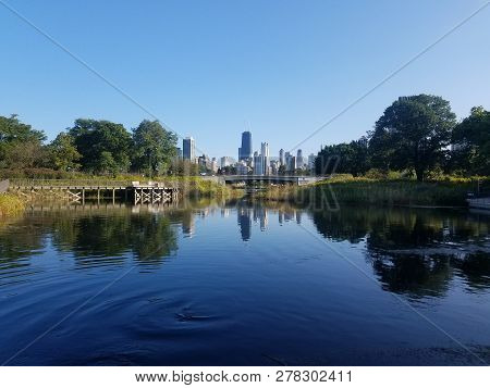 Chicago Skyline Cityscape With John Hancock Center In The Middle And Reflection On A Pond In Lincoln