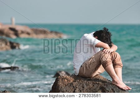 Anxious confused Asian man covering face with hands and bend down head on the rock of sea shore. poster