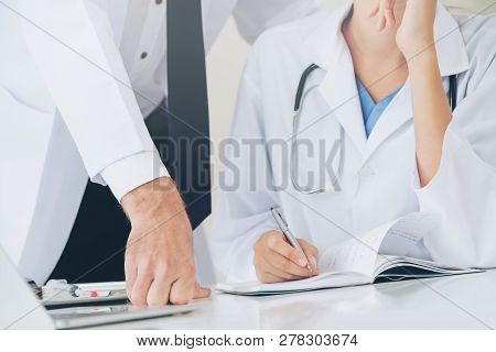 Doctor Writes Report At Desk With Another Doctor.