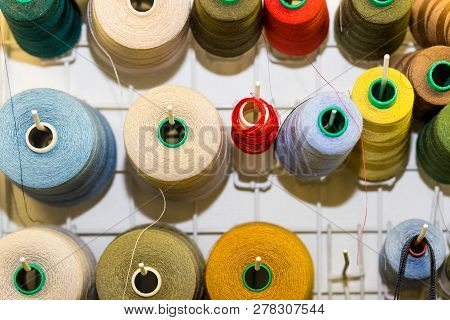 Bobbins with colorful threads on old wooden table background, Sewing background.Interior of sewing workshop.technology, material, equipment, Hobby concept.spools of thread. poster