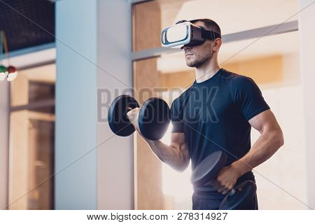 Man Wearing Virtual Reality Glasses With Dumbbells. Athletic Man Performs An Exercise On The Strengt