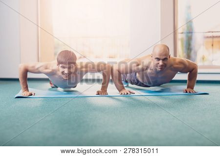 Two Men Will Perform Fitness Training In The Gym. Happy Sports Men Perform A Physical Exercise From