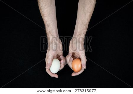 Man Holding One White Egg In His Hand, And One Brown Egg In His Other Hand