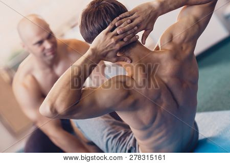 A Man Performs A Physical Exercise On The Crunches. Individual Training In A Fitness Club With A Tra